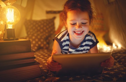 happy child girl with tablet learning Portuguese